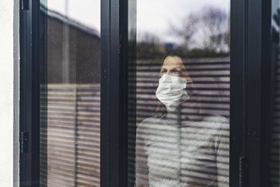 Woman with mask looking out of window Photograph by Justin Paget