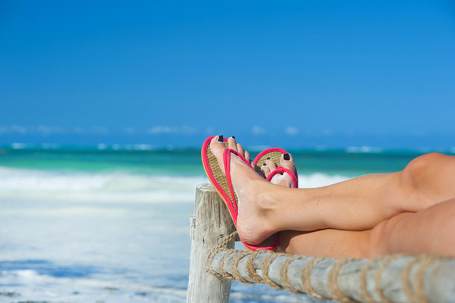 Womans feet with flip-flops at the beach Photograph by Guenterguni