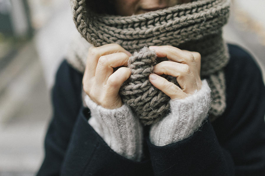 Womans hand holding knitted scarf, close-up Photograph by Westend61