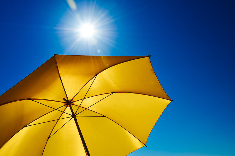 Yellow Umbrella With Bright Sun And Blue Sky Photograph by Grafxart8888