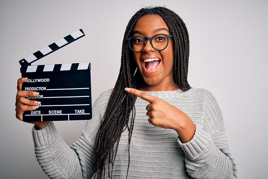 Young african american director girl filming a movie using clapboard over isolated background very happy pointing with hand and finger Photograph by AaronAmat