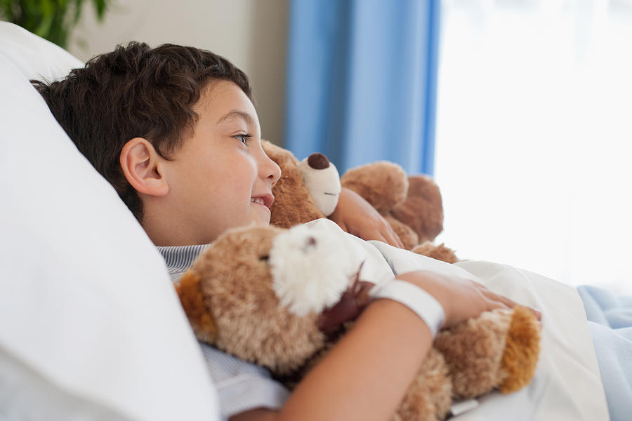 Young boy in hospital bed with teddy bears Photograph by Paul Bradbury