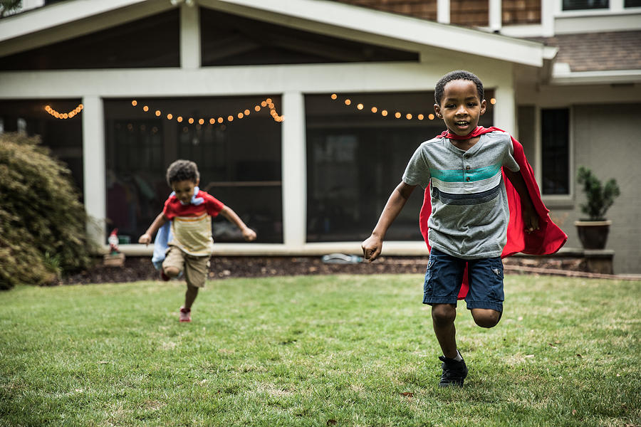 Young boys (3 yrs and 6yrs) in capes playing in backyard Photograph by MoMo Productions