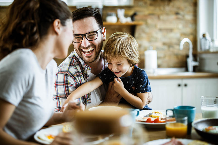 Young cheerful family having fun at dining table. Photograph by Skynesher