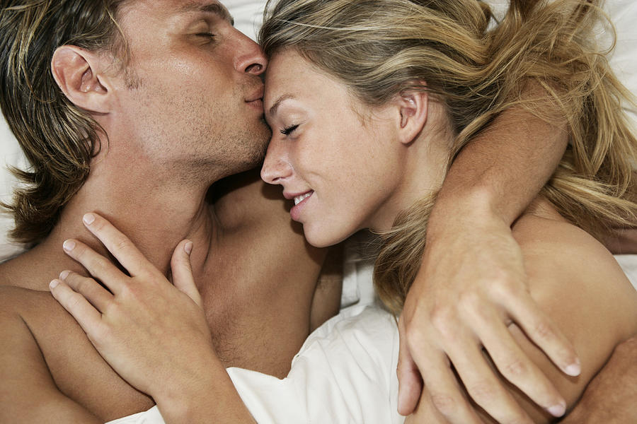 Young couple in bed, man kissing womans forehead, close-up Photograph by Dimitri Otis