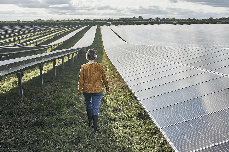 Young female farmer walking through solar farm Photograph by Mike Harrington