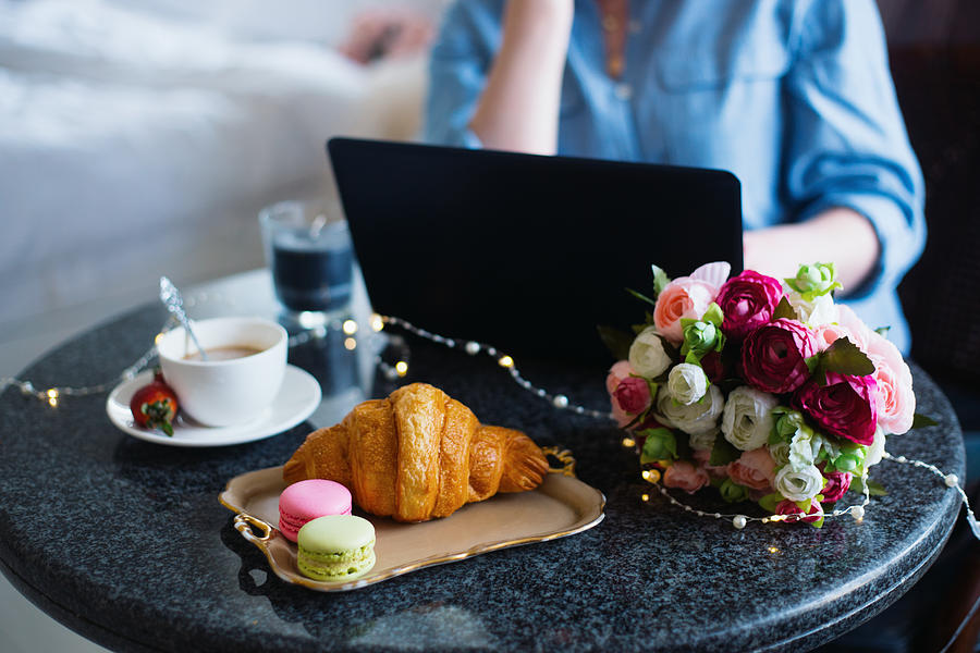 Young woman freelancer in blue shirt working on laptop during lunch with coffee, croissant, macaroons and flowers on table Photograph by Alexa-photo