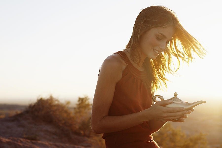Young woman holding genie lamp Photograph by Fotosearch