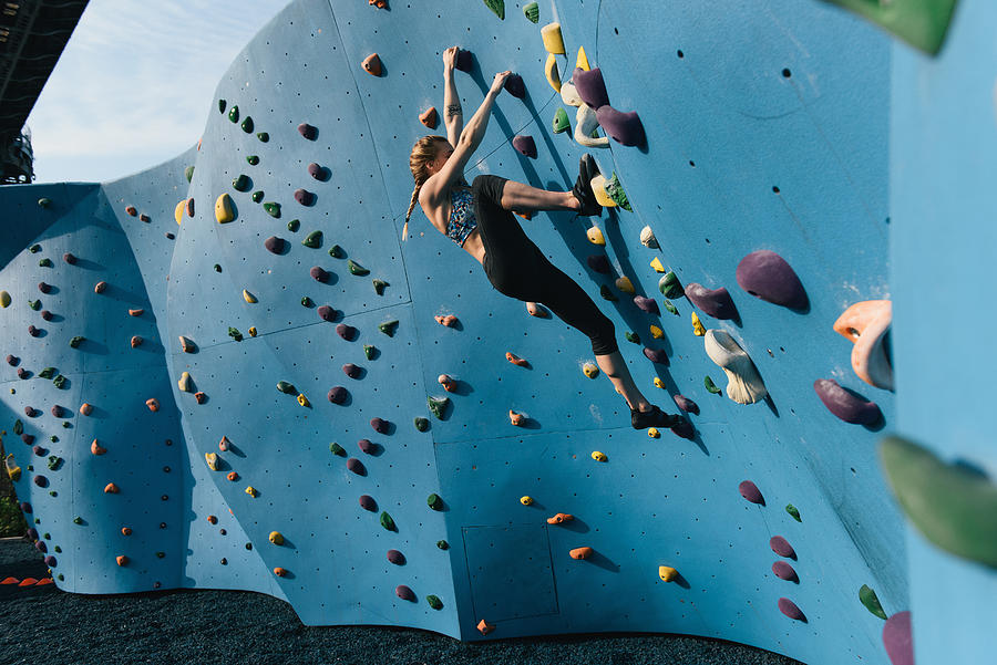 Young woman on climbing wall, Brooklyn Bridge Park, Brooklyn, New York, USA Photograph by Matt Dutile