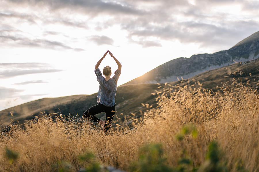 Young woman preforms yoga in mountains in morning light Photograph by AscentXmedia