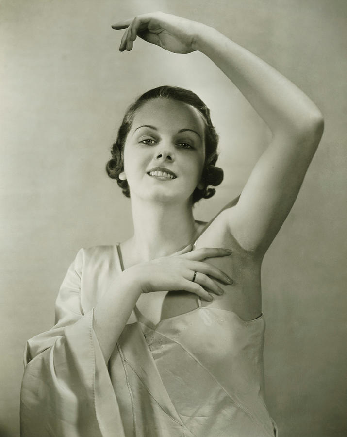 Young woman raising hand, posing in studio, (B&W), portrait Photograph by George Marks