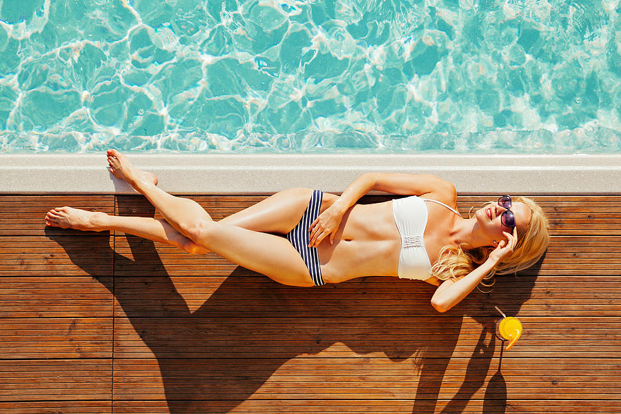 Young woman sunbathing by the swimming pool Photograph by EmirMemedovski