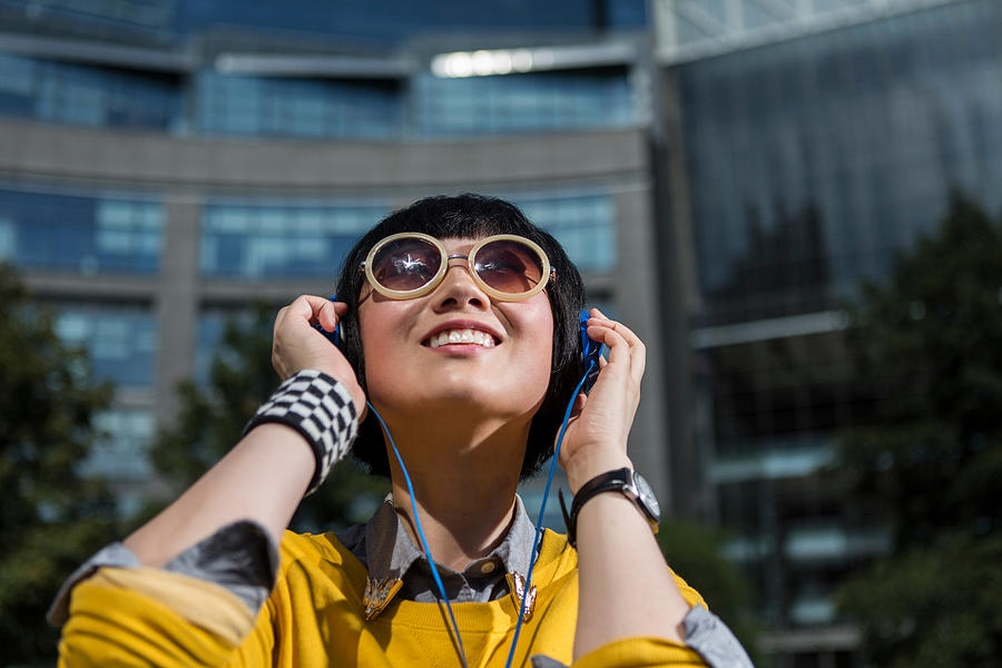 Young woman wearing sunglasses and headphones looking up Photograph by Steve Prezant