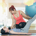 Asian Woman Fitness Coach Teach Her Student For Rubber Ball Exer by Anek Suwannaphoom