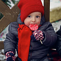 Baby In Red Hat Sits On A Bench In The Street With Candy by Elena Saulich