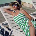 Girl Lies On A Chaise Longue In A Green Striped Dress by Elena Saulich