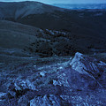 Light On Stone Mountain Slope With Forest At Night by Michael Pelin