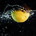 Orange Splashing In Water by Trond Kristensen