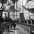 people walking over the brooklyn bridge between cables towards lower manhattan New York City USA by Joe Fox