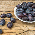 Plate Full Of Fresh Plums On A Wooden Background by Ranko Maras