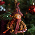 Silly Old Monkey Toy In A Child Hands Under The Christmas Tree by Andrea Varga
