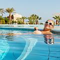 Young Woman Enjoying Warm Water In Pool by Nikita Buida