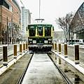 Streetcar Waiting For Passengers In Snowstrom In Uptown Charlott by Alex Grichenko