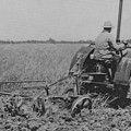 A Farmer Driving A Tractor by American School