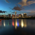 Clouds Roll Over The Austin Skyline As The Neon Reflects In The Glass-like Waters Of Lady Bird Lake by Austin Welcome Center