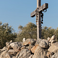 Rosary Hanging On A Small Wooden Cross On A Stone Wall by Stefan Rotter