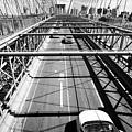traffic vehicles driving over the worn tarmac on brooklyn bridge New York City USA by Joe Fox