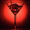 Cocktail Glass With Splashes On Red Background by Oleg Yermolov