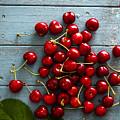 Fresh Cherries On Wood by Mythja Photography