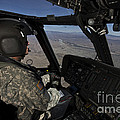 Pilot Operating The Cockpit Of A Uh-60 by Terry Moore