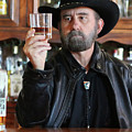 A Bearded Cowboy In Black Contemplates His Whiskey In A Saloon by Derrick Neill