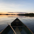 A Boat And Paddle On A Tranquil Lake by Keith Levit