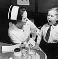 A Nurse Examining The Teeth Of A Boy by Everett