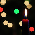 A Red Christmas Candle With Blurred Lights by Derrick Neill