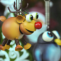 A Rudolph The Red Nosed Reindeer Ornament With A Penguin by Derrick Neill