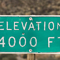 A Weathered Elevation Sign On Highway by Rich Reid
