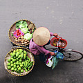 Aerial View Of A Vietnamese Traditional Seller On The Bicycle With Bags Full Of Vegetables by Srdjan Kirtic