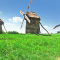 Ancient Windmills In Field by Nataly Raikhel