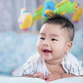 Asian Newborn Baby Smile In A Bed With Fish And Animal Mobile by Anek Suwannaphoom