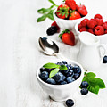 Berries In Bowls  On Wooden Background. by Natalia Klenova