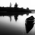 Black And White Canoe In Still Water by Karl Anderson