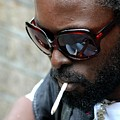 Black Male Busker With Sunglasses Cigarette And Skull Pendant London England by Imran Ahmed