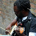 Black Street Musician Sits Against Wall Plays Guitar London England by Imran Ahmed
