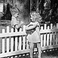 Boy And Girl Talking Over Fence, C.1940s by H. Armstrong Roberts/ClassicStock