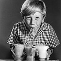 Boy Drinking Three Shakes At Once by Debrocke/ClassicStock