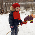 Boy On A Toy Horse Is Standing On The Street In Winter by Elena Saulich